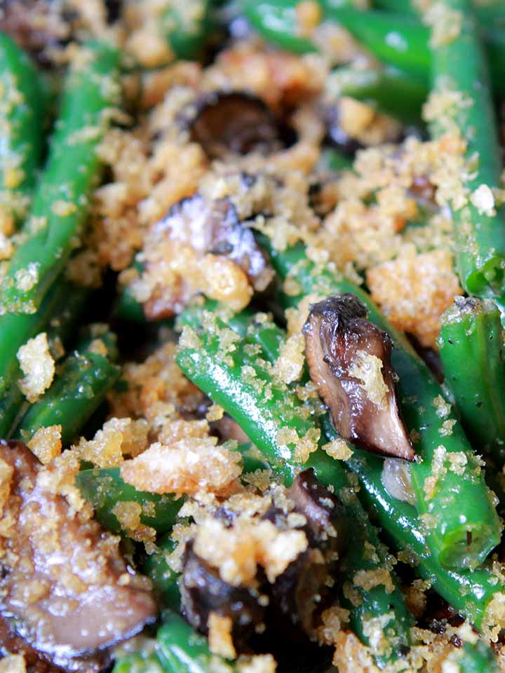 A close up on green beans in mushroom cream sauce with crushed pork rinds on top