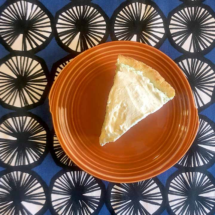 a slice of gluten free Jello Cream pie on an orange plate against a blue patterned background