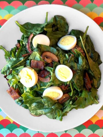 a plate of Keto Spinach Salad with Warm Bacon Dressing