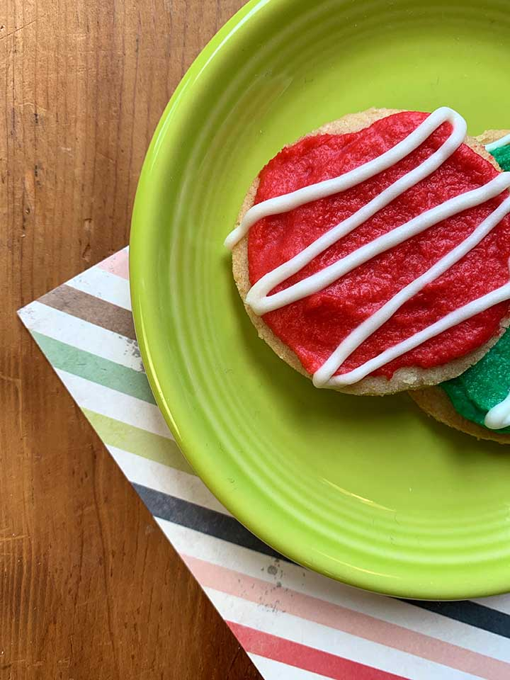 a top down view of a red frosted sugar free Christmas cookie on a green plate