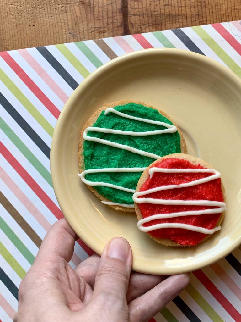 a hand hold a plate holding one green and 1 green frosted holiday shortbread cookie