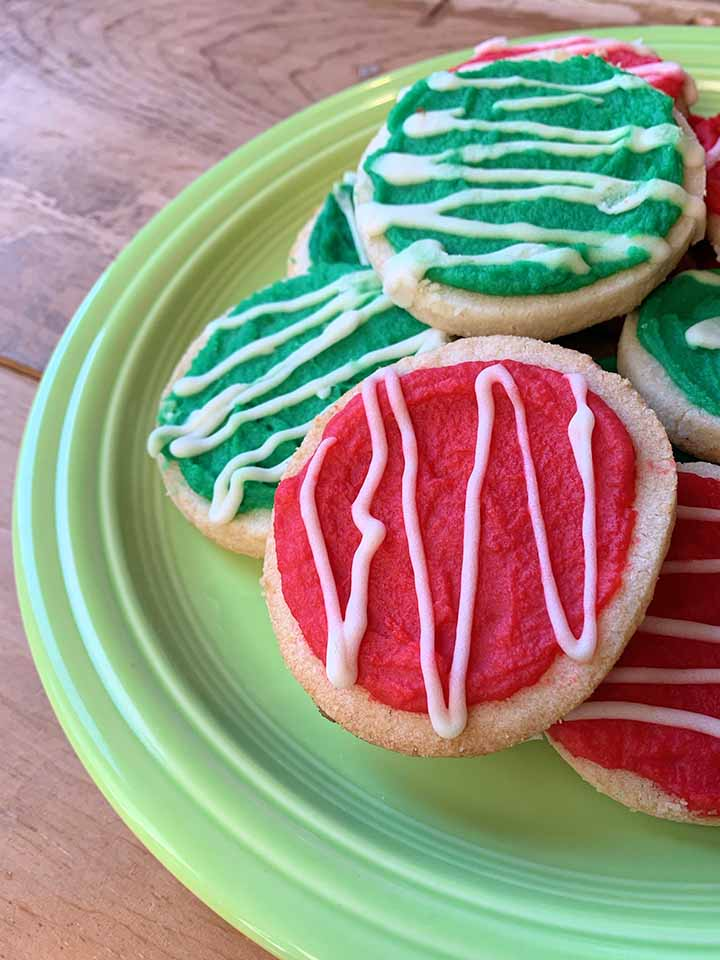 several red and green sugar free holiday cookies on a green plate