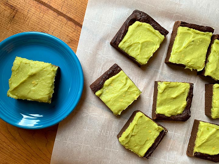 a top down view of a keto avocado brownie on a blue plate and 5 brownies on white parchment paper