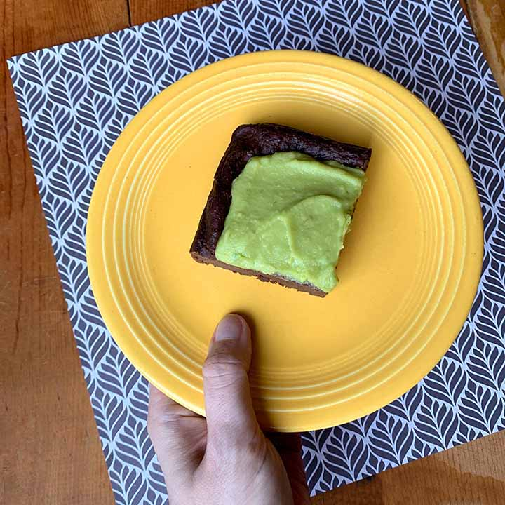 a hand holds a yellow plate with a gluten free dairy free avocado brownie