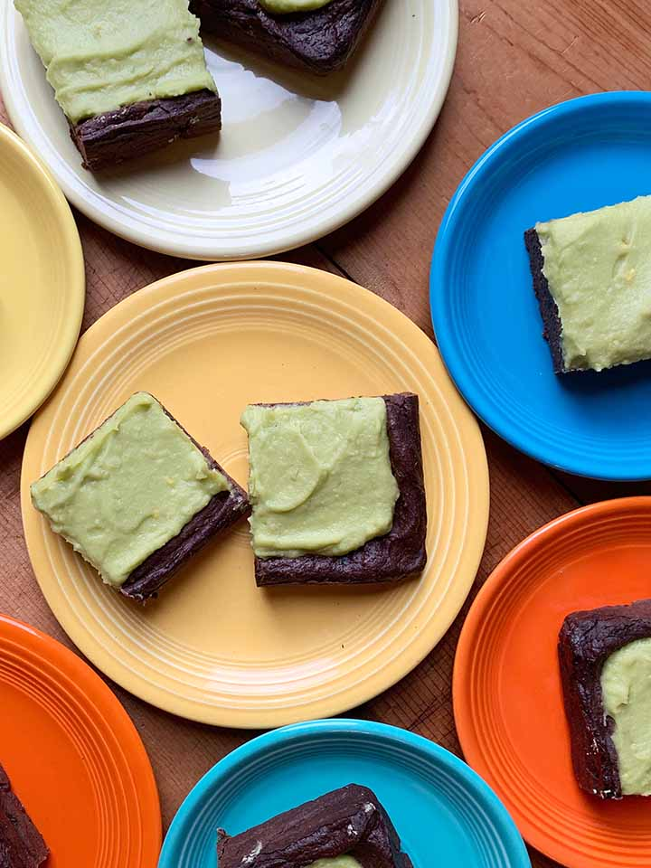 Multiple colored plates hold slices of easy avocado brownies