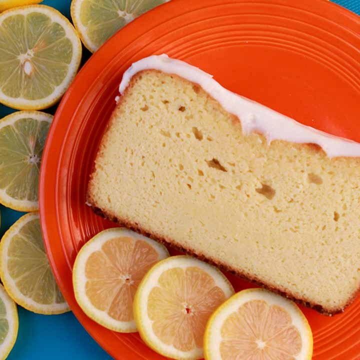 a top down shot of a slice of Keto Lemon Pound Cake on an orange plate, surrounded by lemon slices