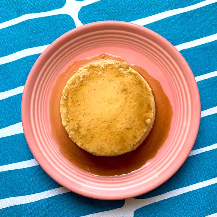 top down image of a piece of Keto creme caramel on a pink plate against a blue patterned background