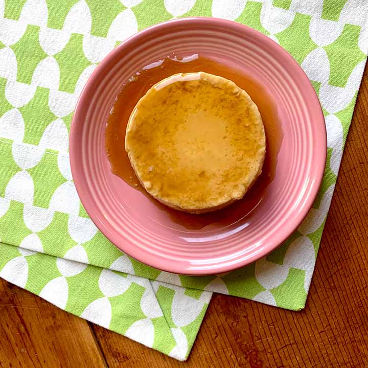 a piece of grain free flan on a pink plate against a white and green patterned background