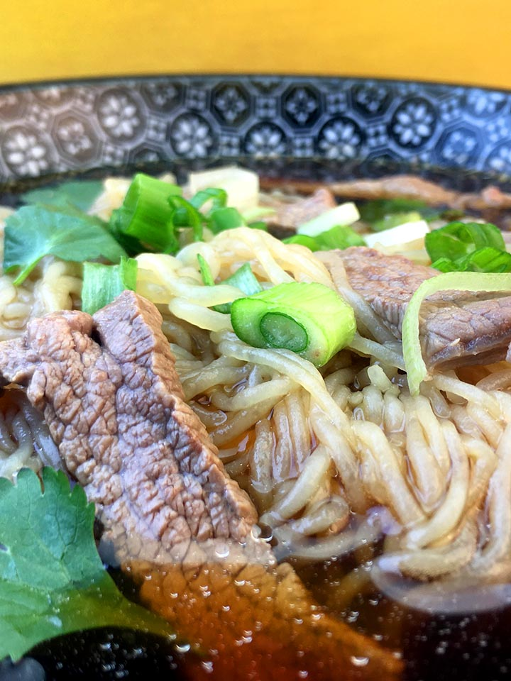 a close up image of a bowl of low carb beef pho