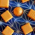 orange creamsicle gummies against a blue background