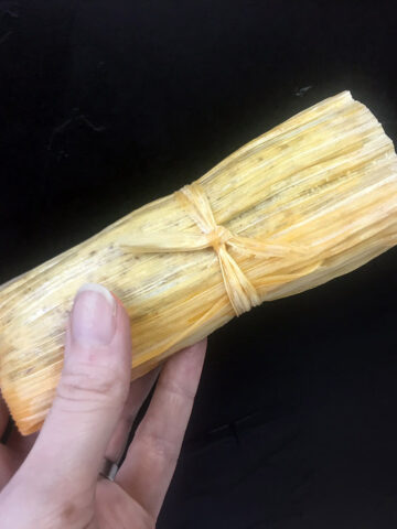 a hand holds a Keto Beef Tamale