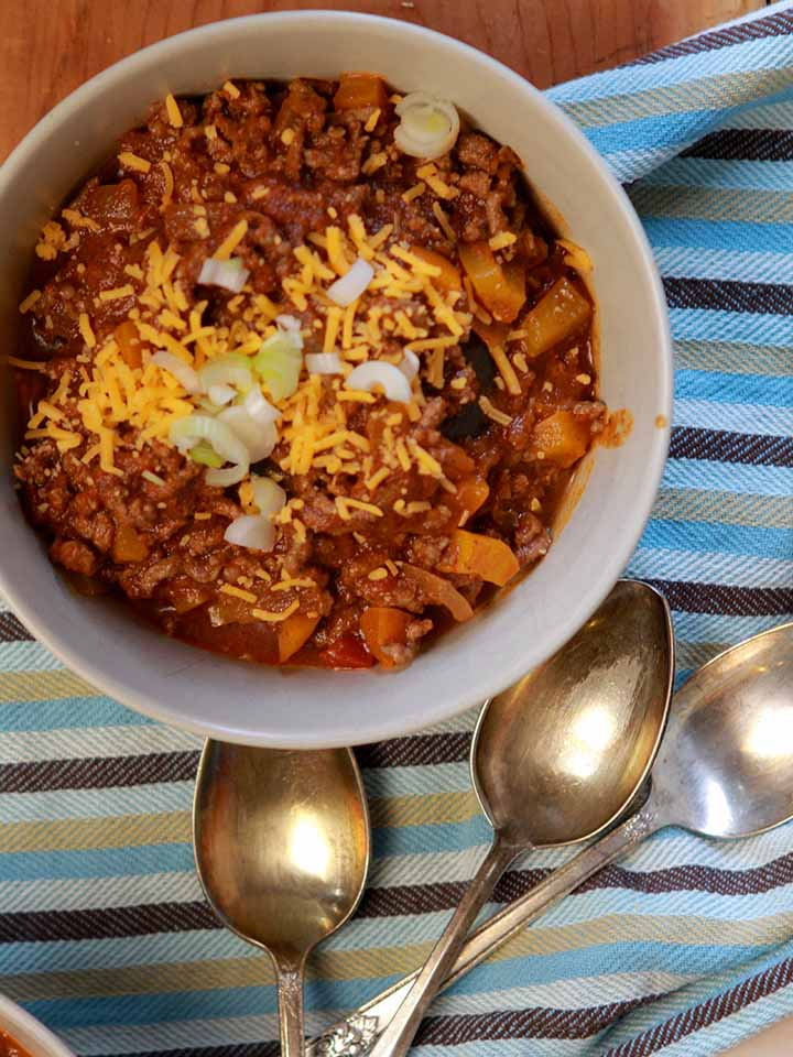 a top down view of a bowl of Keto chili con carne and several spoons
