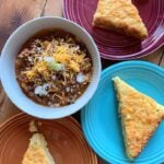 a top down view of a bowl of classic chili con carne and colorful plates of low carb cheesy jalapeno cornbread