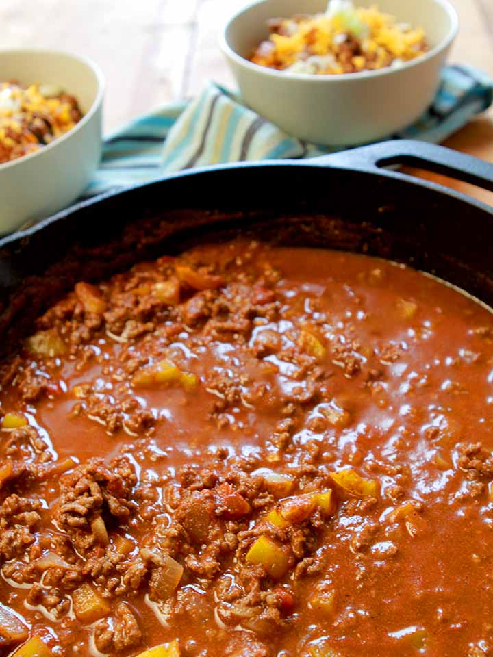 a cast iron pan holding easy chili con carne with bowls of the chili in the background