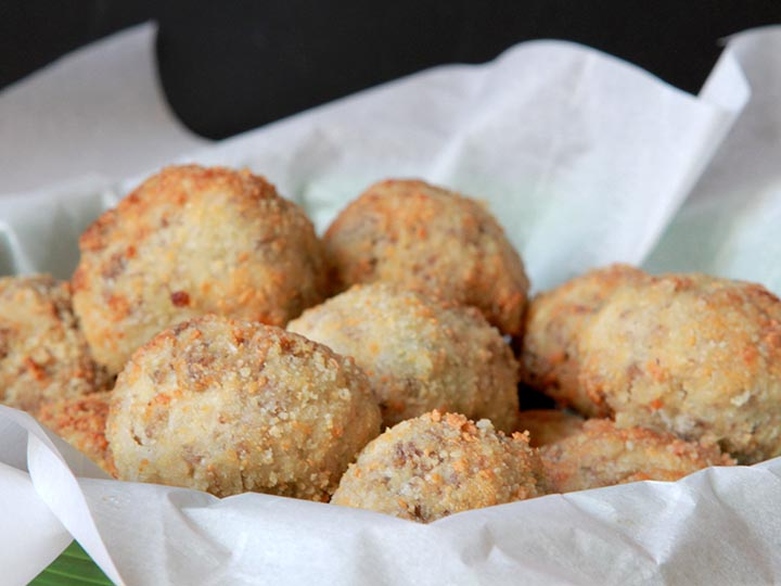 A basket filled with low carb sauerkraut balls against a black background