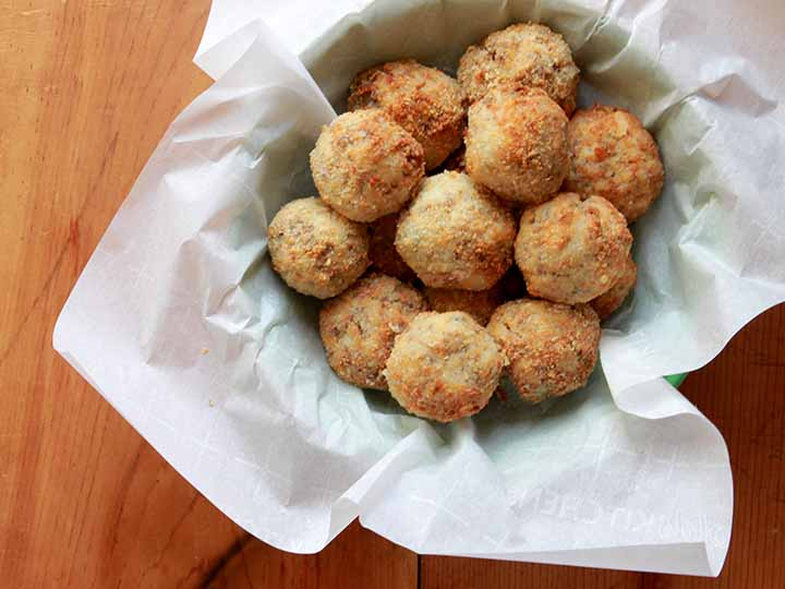 A basket filled with low carb sauerkraut balls against wooden tabletop