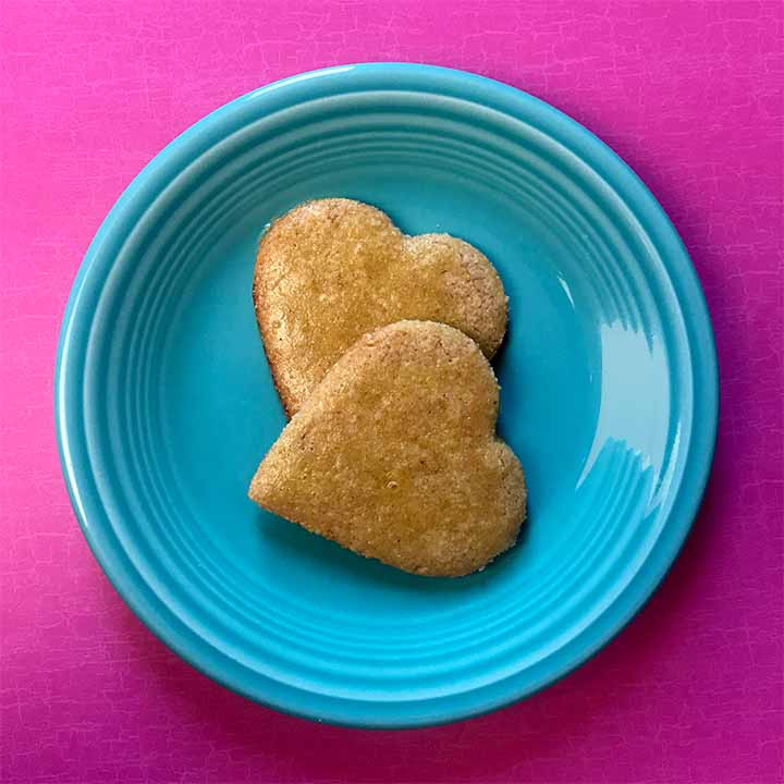 2 Keto gingerbread cookies on a blue plate against a bright pink background