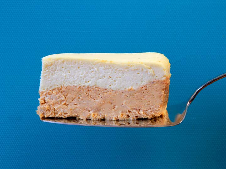 A slice of 2 layer Keto pumpkin cheesecake against a bright blue background