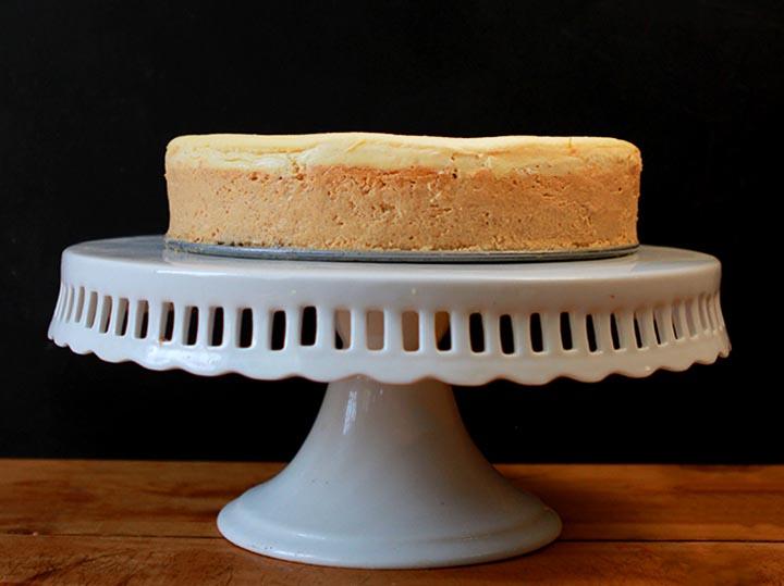 A sugar-free Keto pumpkin cheesecake on a white pedestal