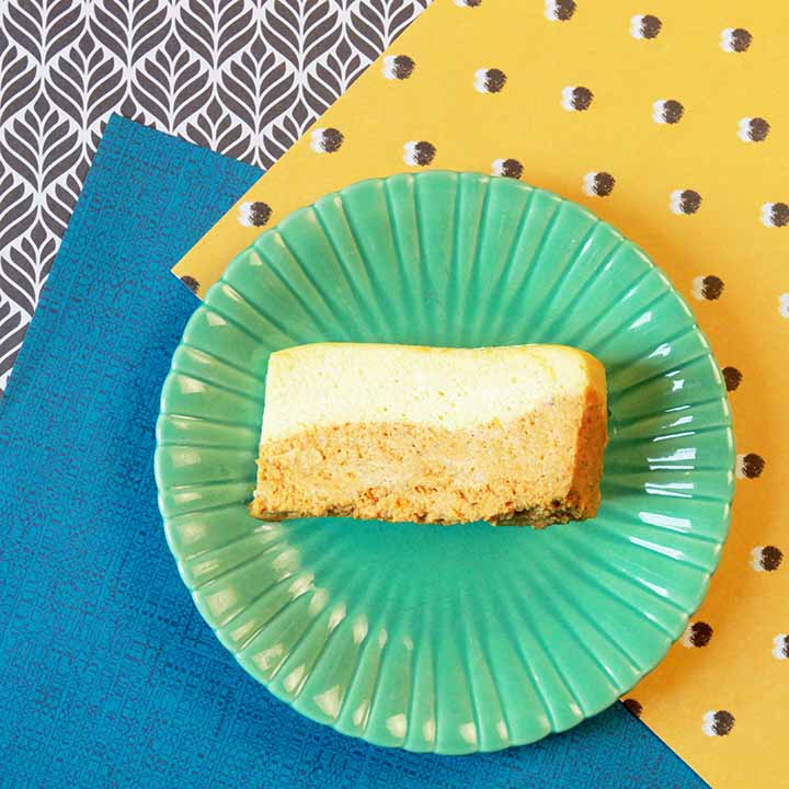 a slice of NY style layered pumpkin cheesecake against crazy patterned backgrounds