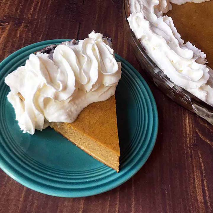 a slice of Keto pumpkin pie on a blue plate with a pumpkin pie in the background