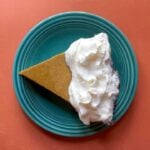 a slice of low carb pumpkin pie on a blue plate against an orange background