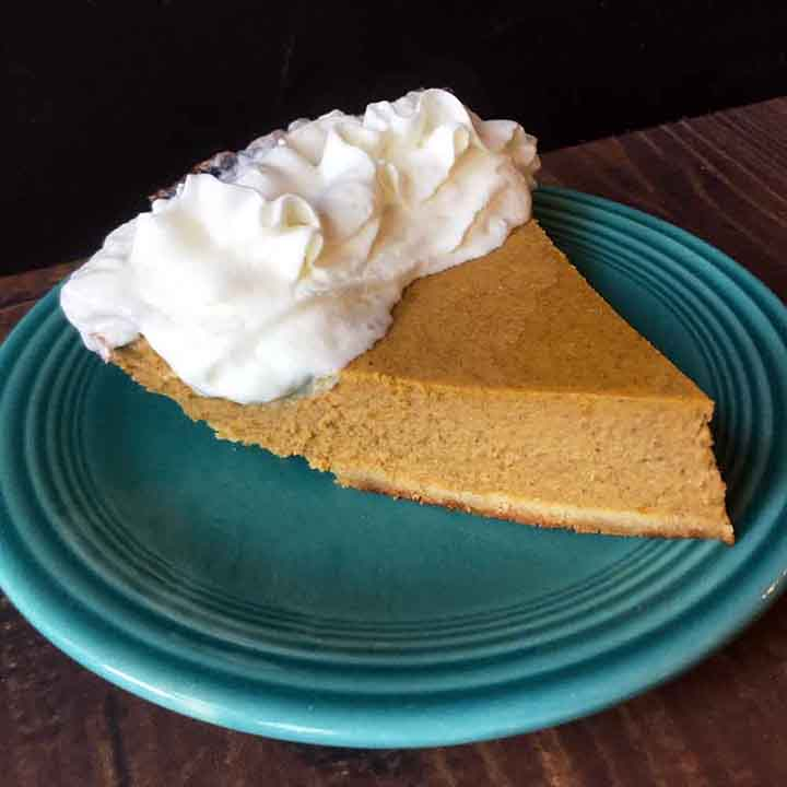 A side view of a slice of gluten free pumpkin pie on a blue plate