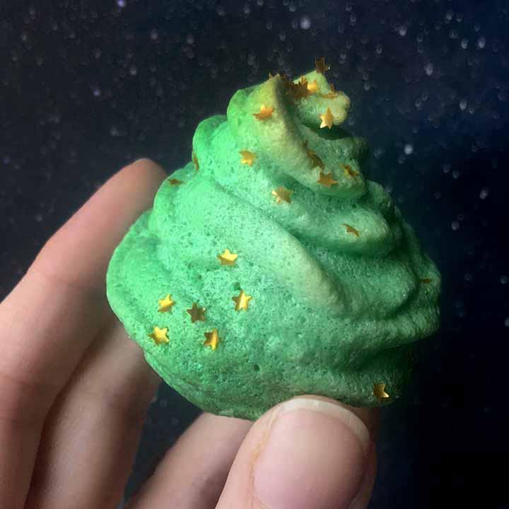 a hand holds a Keto christmas tree meringue cookie