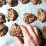 a hand picks up a Keto Chocolate Meringue Cookies