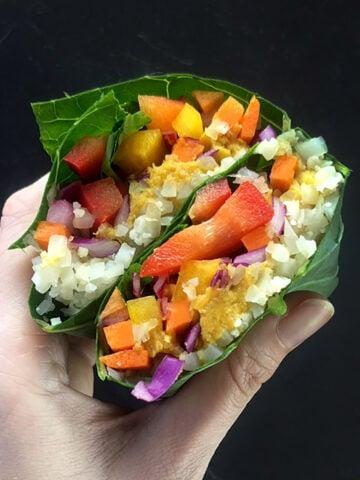 a hand holds a Keto Rainbow Veggie Wrap