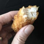 a hand holds a fish stick from fish and chips