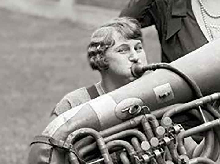 a closer image of an old timey woman playing a huge horn