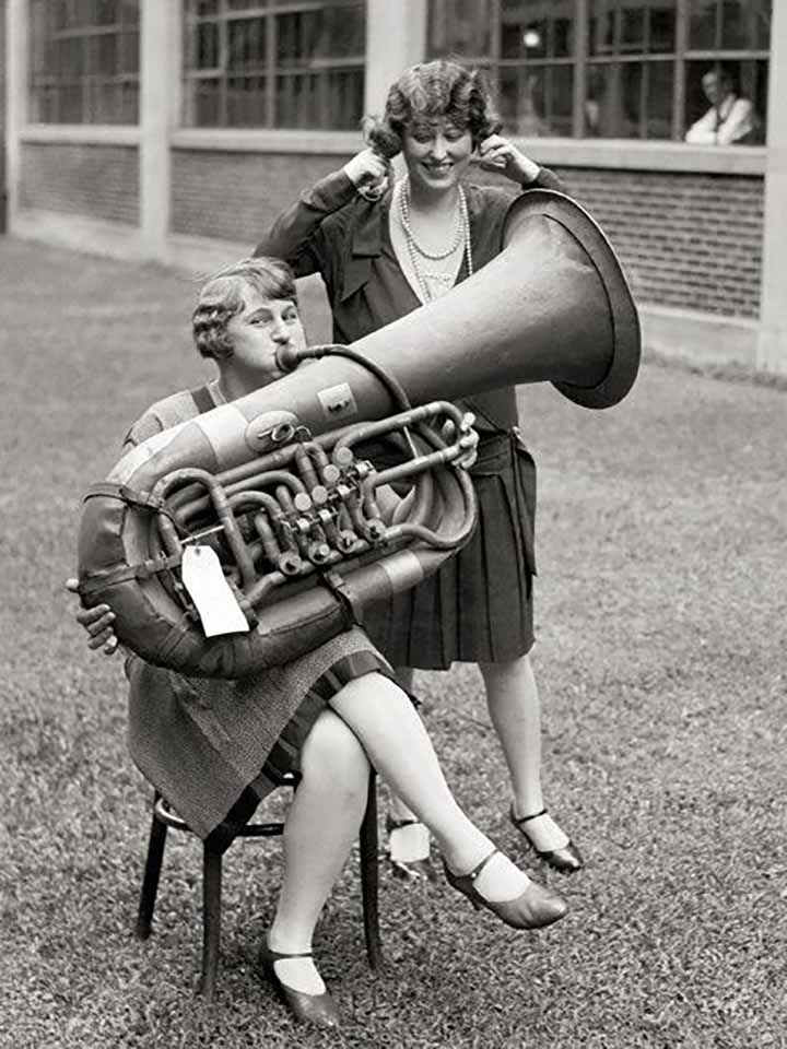 Old Timey Photograph of a woman playing a huge horn