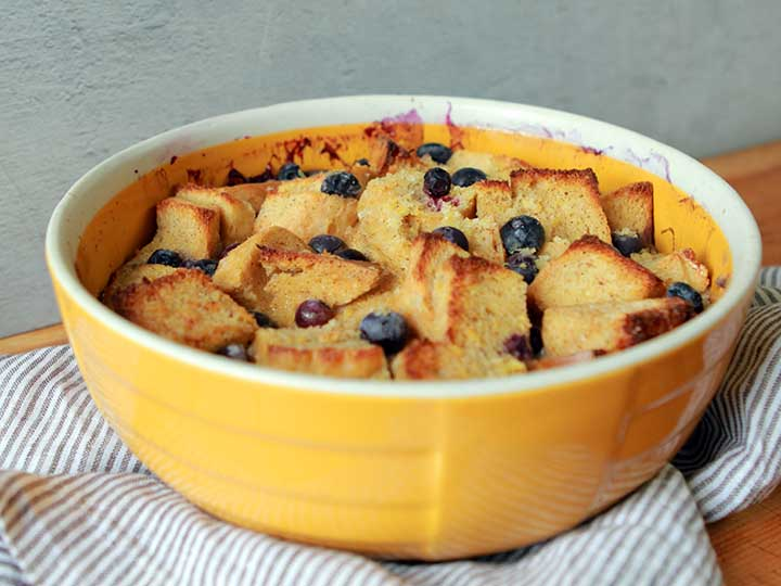 A yellow casserole dish holds Low Carb Keto Blueberry Bread Pudding with Caramel Sauce