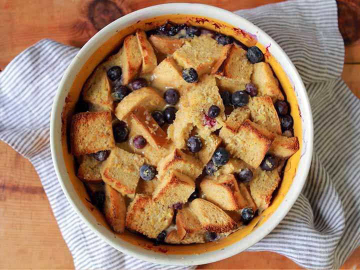 Top down view of a yellow casserole dish holds Low Carb Keto Blueberry Bread Pudding with Caramel Sauce