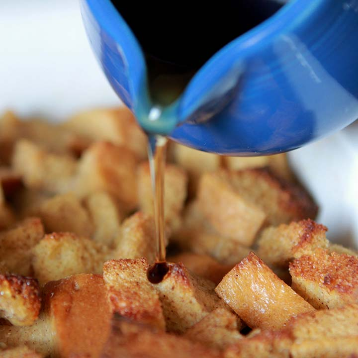 Close Up image of syrup being poured onto a slice of French Toast Breakfast Casserole