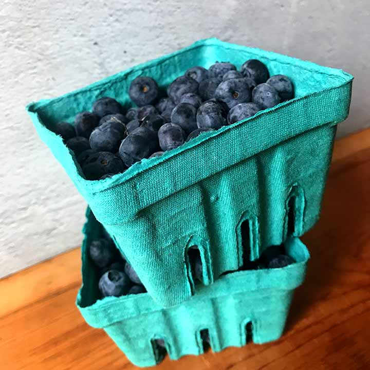 2 green containers filled with blueberries