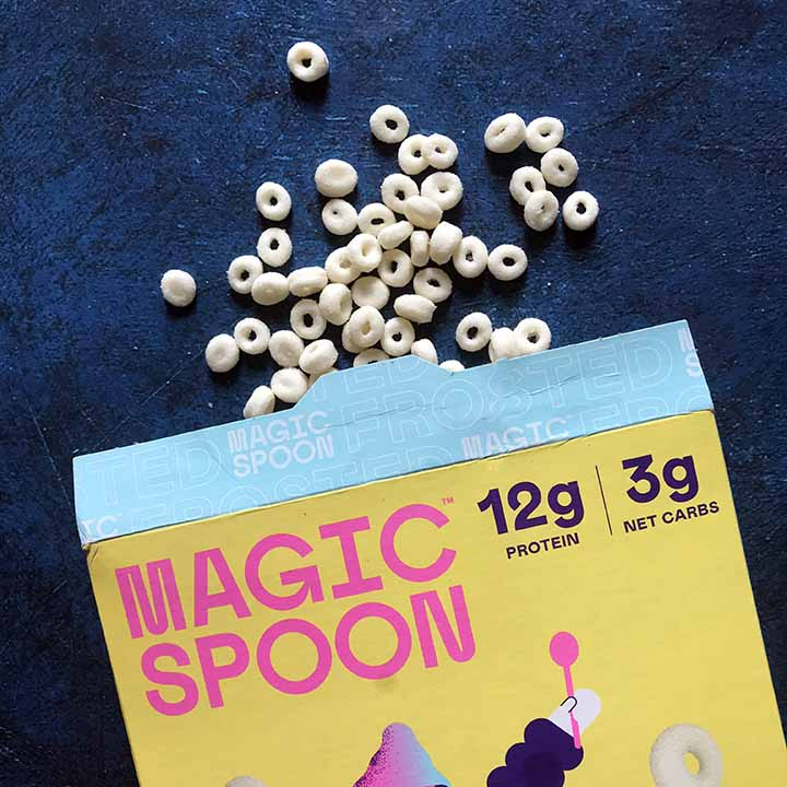 a open box of Magic Spoon Low Crab Cereal with cereal spilling out against a blue background