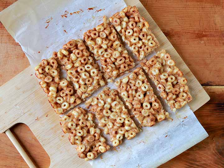 a top down view of 8 low carb keto cereal bars on white parchment paper against a wooden tabletop