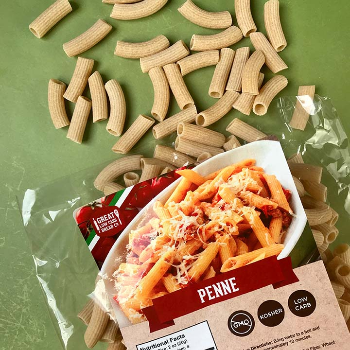 A bag of Great Low Carb Bread Co Penne noodles with noodles spilling out