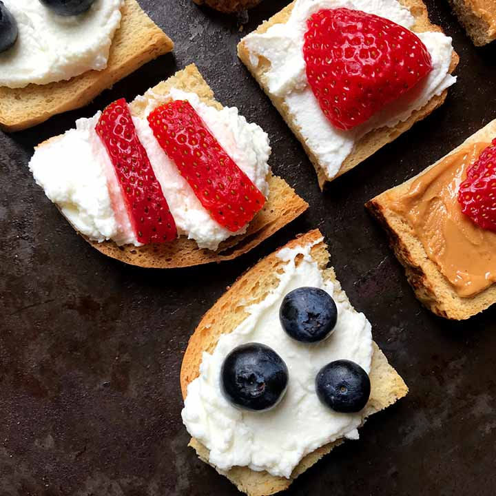 Close up shot of low carb melba toast with cream cheese and berries