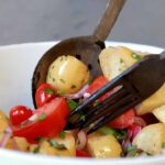 A large wooden knife and spoon pick up a serving of low carb Italian Bread Salad