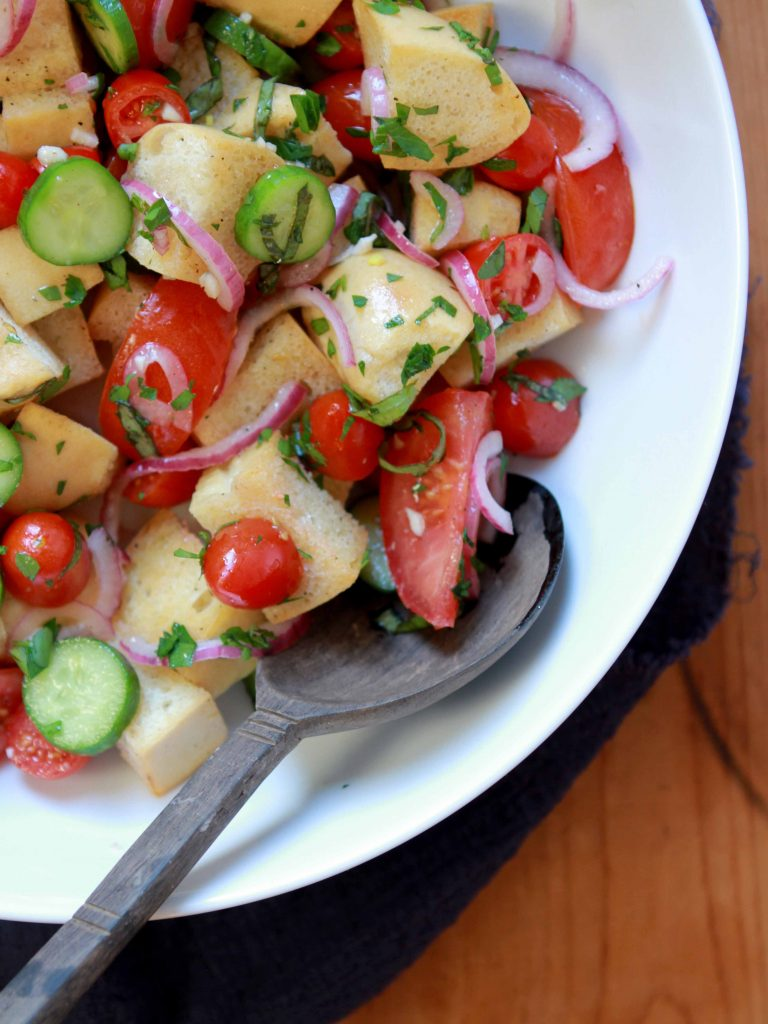 A top down view of a serving bowl of Keto Panzanella Italian Bread Salad with a spoon