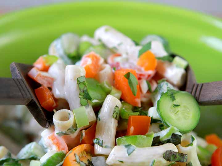 A wooden salad fork and spoon are picking up a serving of real low carb macaroni salad