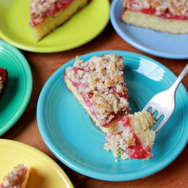 A forkful of low carb keto strawberry crumb cake against a blue plate