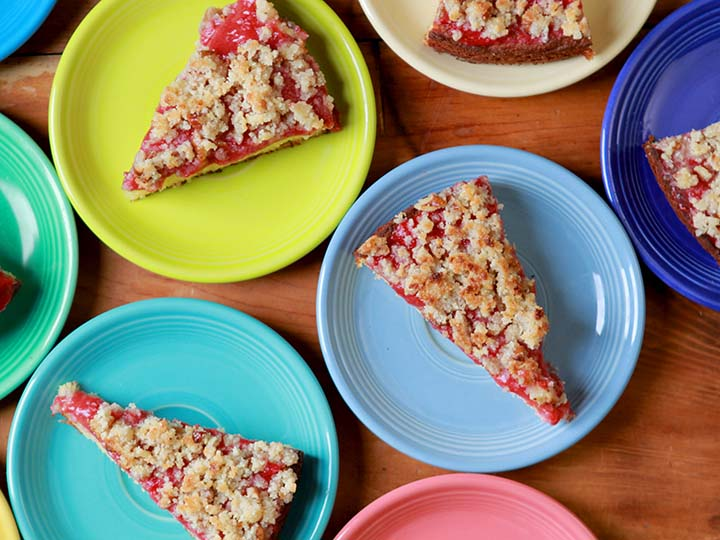 Green, blue and pink plates hold slices of low carb keto strawberry coffee cake