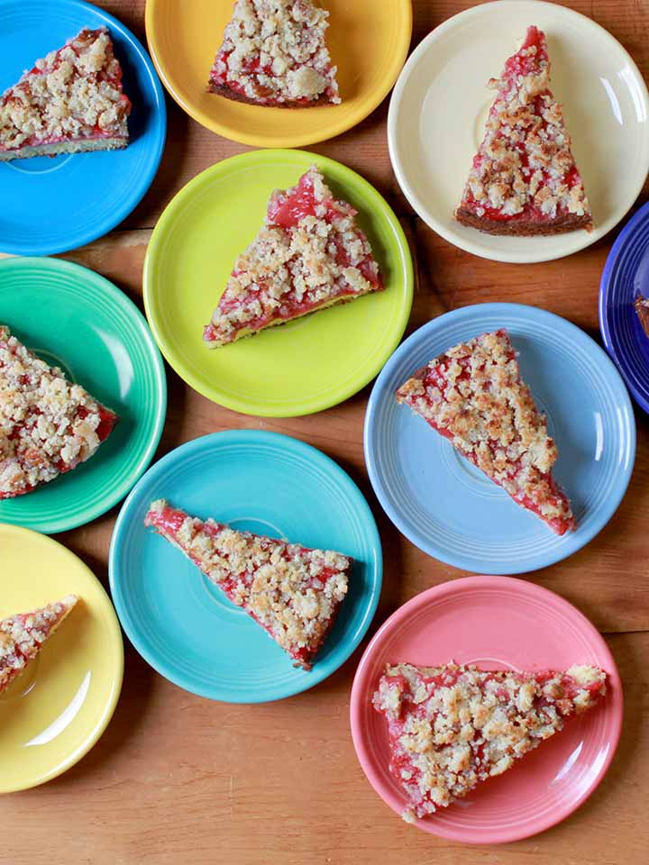 Top down shot of colorful plates holding slices of healthy strawberry streusel cake