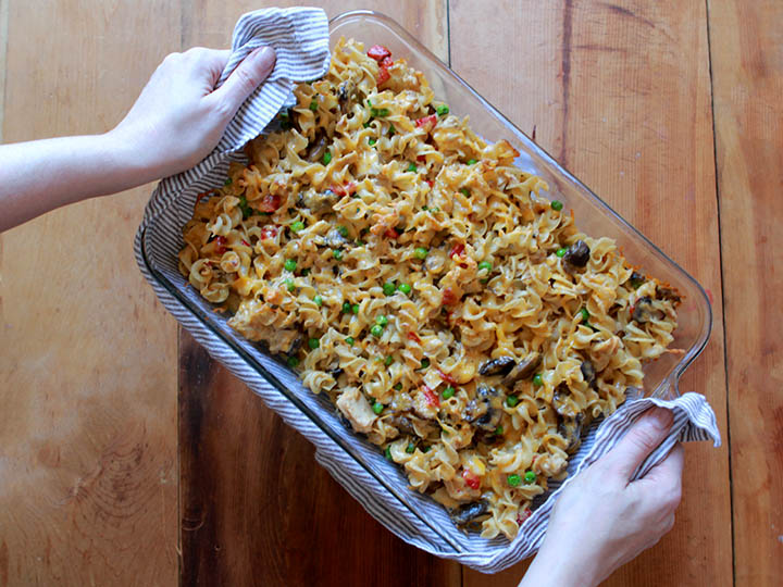 Two hands hold a pan of keto tuna noodle casserole