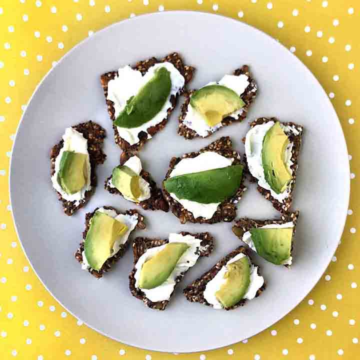 A plate holding Multi Seed Crackers topped with cream cheese and avocado