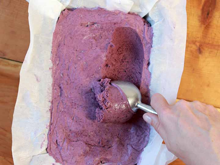 A hand scoops out a spoonful of a Blueberry Keto Frozen Treat